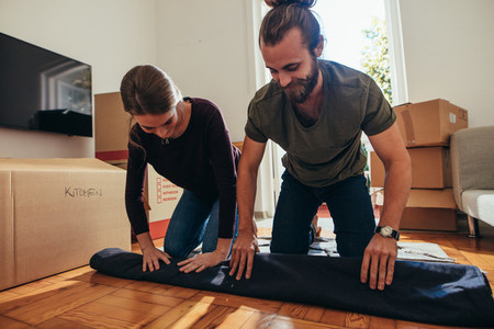 Couple sitting on a carpet and rolling it for packing