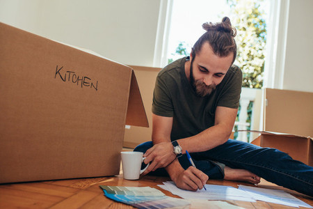 Man making a list of articles for packing