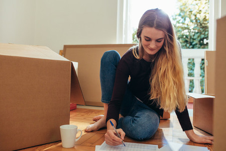 Woman making a list of articles for packing
