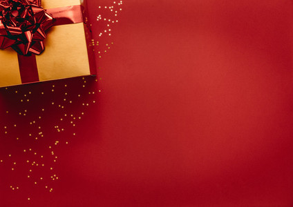 Golden coloured gift box with stars on red background