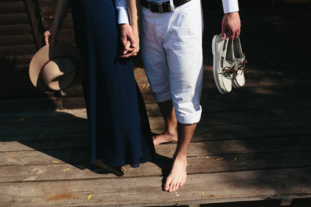 couple walk barefoot on pier