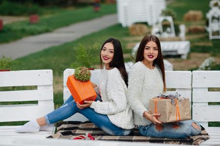 Two beautiful girls holding gifts