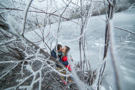 Couple in winter forest near lake