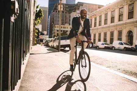 Smiling businessman going to work on bike