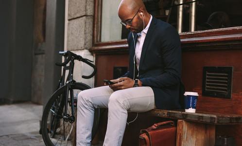Businessman listening music from smart phone outdoors