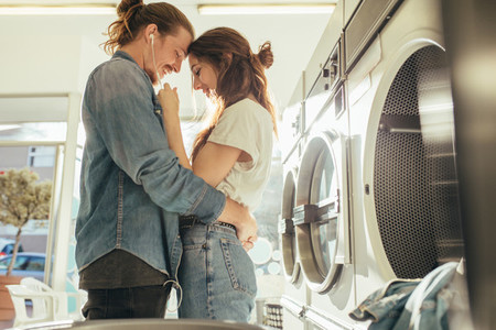 Happy couple embracing each other standing in a laundry room