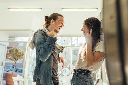 Happy couple listening to music sharing earphones