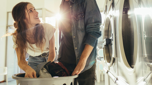 Couple doing laundry together picking clothes from a basket