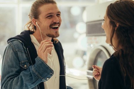 Smiling couple listening to music on earphones
