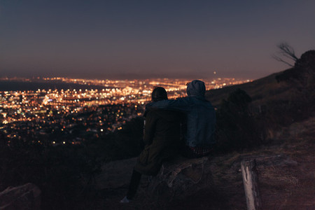 Couple sitting on a hilltop looking at the cityscape below