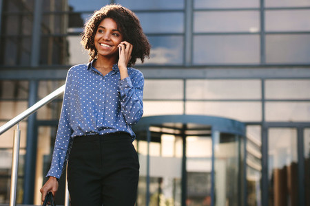 Businesswoman walking outdoors and talking on phone