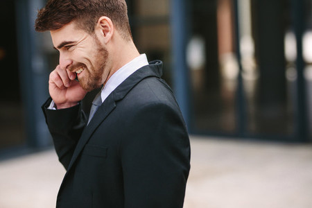 Smiling businessman talking over cell phone