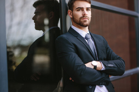 Portrait of confident businessman standing by office building