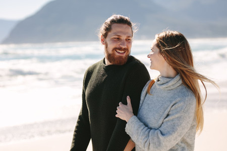 Handsome man walking with his girlfriend at the beach