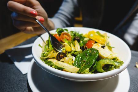 Girl eating healthy salad with o