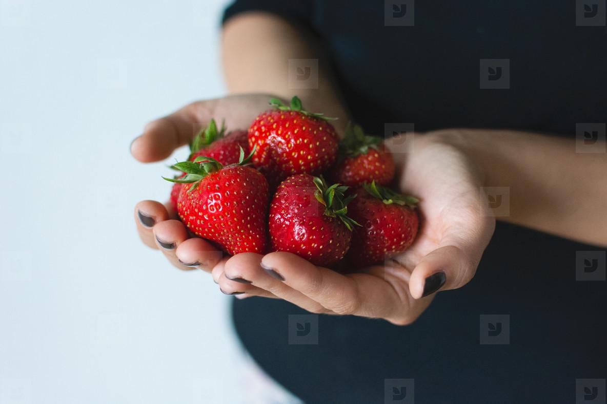 Lady holding fresh strawberries