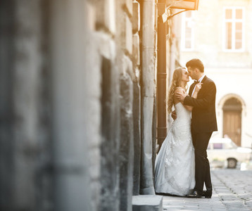 Lovely wedding couple kissing in the city