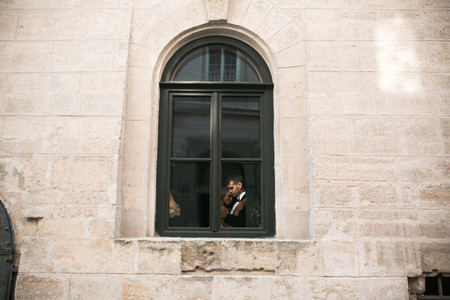 Wedding couple kissing in the window