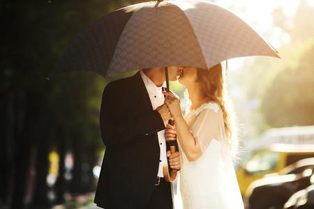 Lovely couple kissing on umbrella