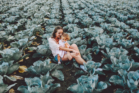 Mother and daughter on the field with cabbage