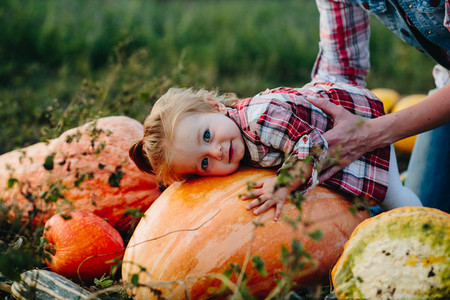 daughter lying on a pumpkin