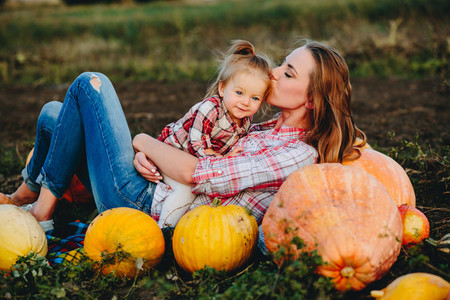 mother and daughter lie between pumpkins