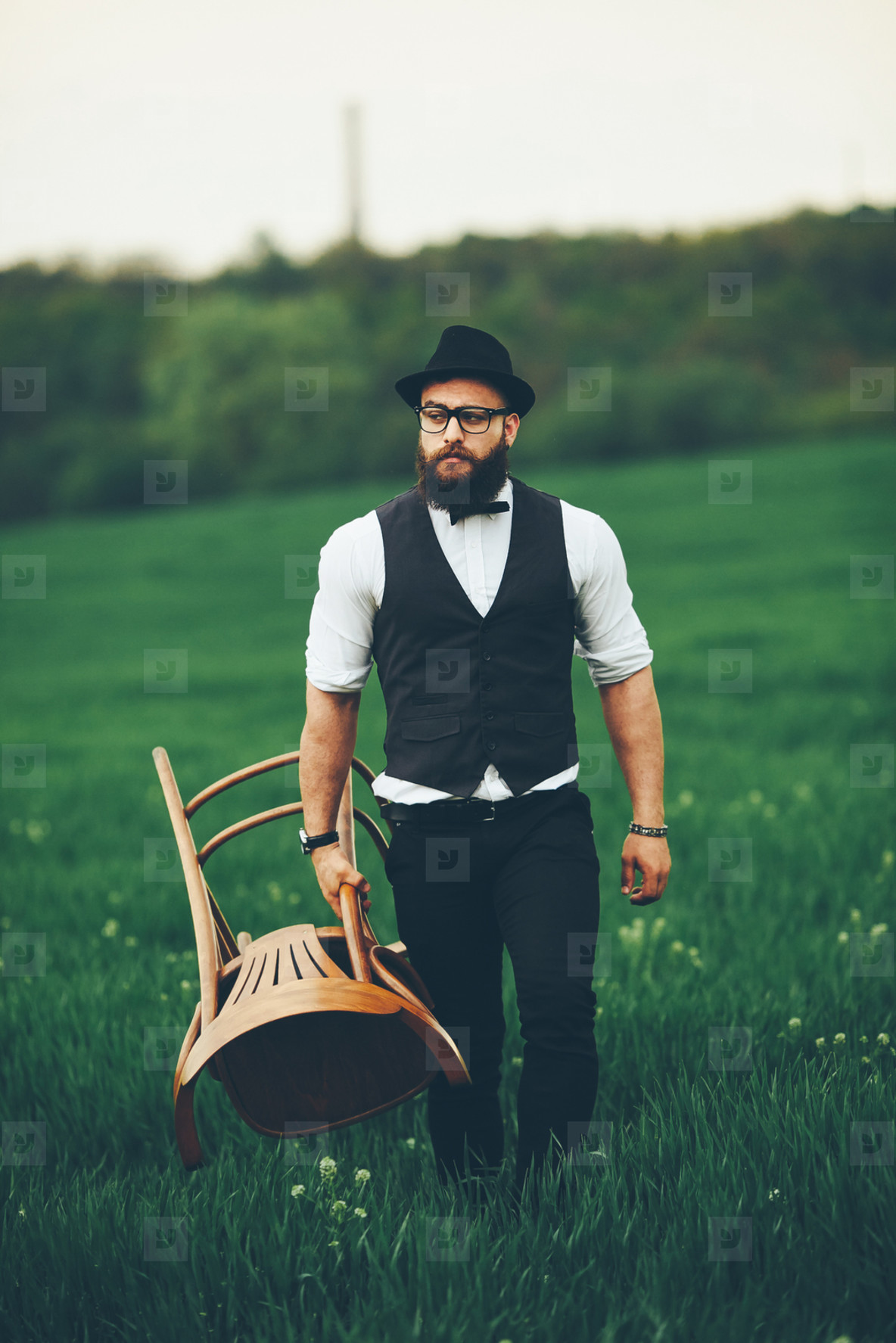 Bearded man carries a chair on the field