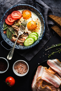 Breakfast set  Pan of fried eggs with bacon  fresh tomato  cucumber  sage and bread