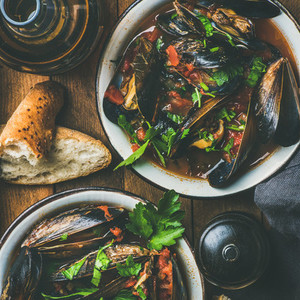 Belgian boiled mussels in tomato sauce with parsley  square crop