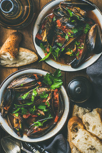 Boiled mussels in tomato sauce and beer over rustic background