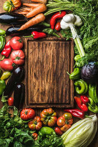 Fresh raw vegetable ingredients for healthy cooking or salad making with rustic wood board
