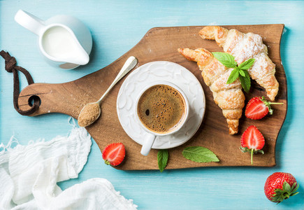 Breakfast or dessert set Freshly baked croissants with strawberries cup of coffee and milk