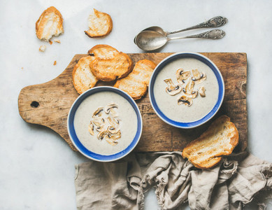 Creamy mushroom soup in bowls with toasted bread marble background