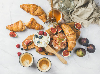 Breakfast with croissants ricotta coffee and berries over marble background