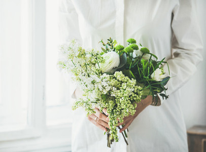 Young woman wearing white clothes holding white flowers bouquet