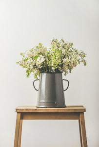 Spring bouquet of white lilacs in vintage enamel vase