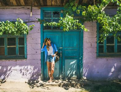 Girl standing near purple wall in Turkish village in summer