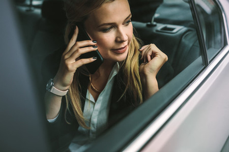 Businesswoman talking on the cellphone in car