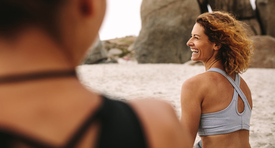 Cheerful women in fitness wear sitting on the beach