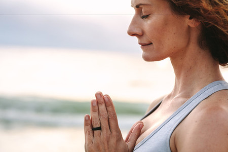Close up of a woman doing yoga standing at the beach