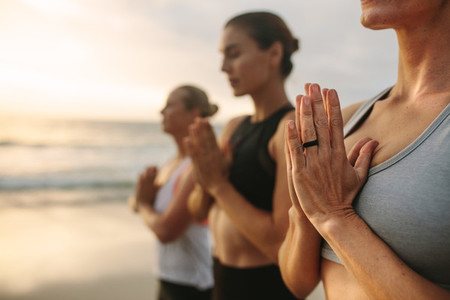 Three women meditating at the beach