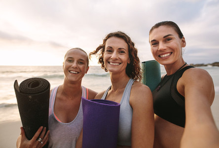 Smiling fitness women standing at the beach with yoga mats in ha