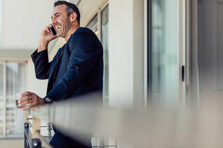 Businessman in hotel room balcony talking on mobile phone