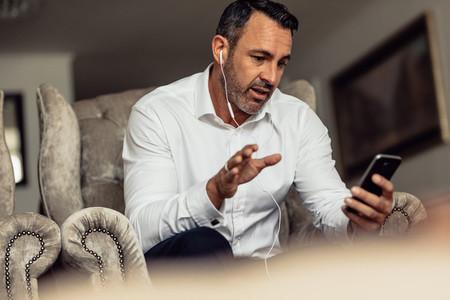 Businessman wearing earphones talking on phone