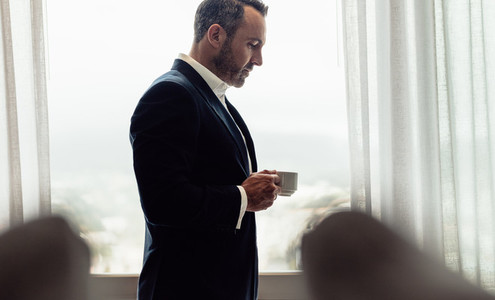 Businessman standing in hotel room having coffee