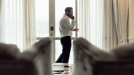 Businessman talking over phone in hotel room