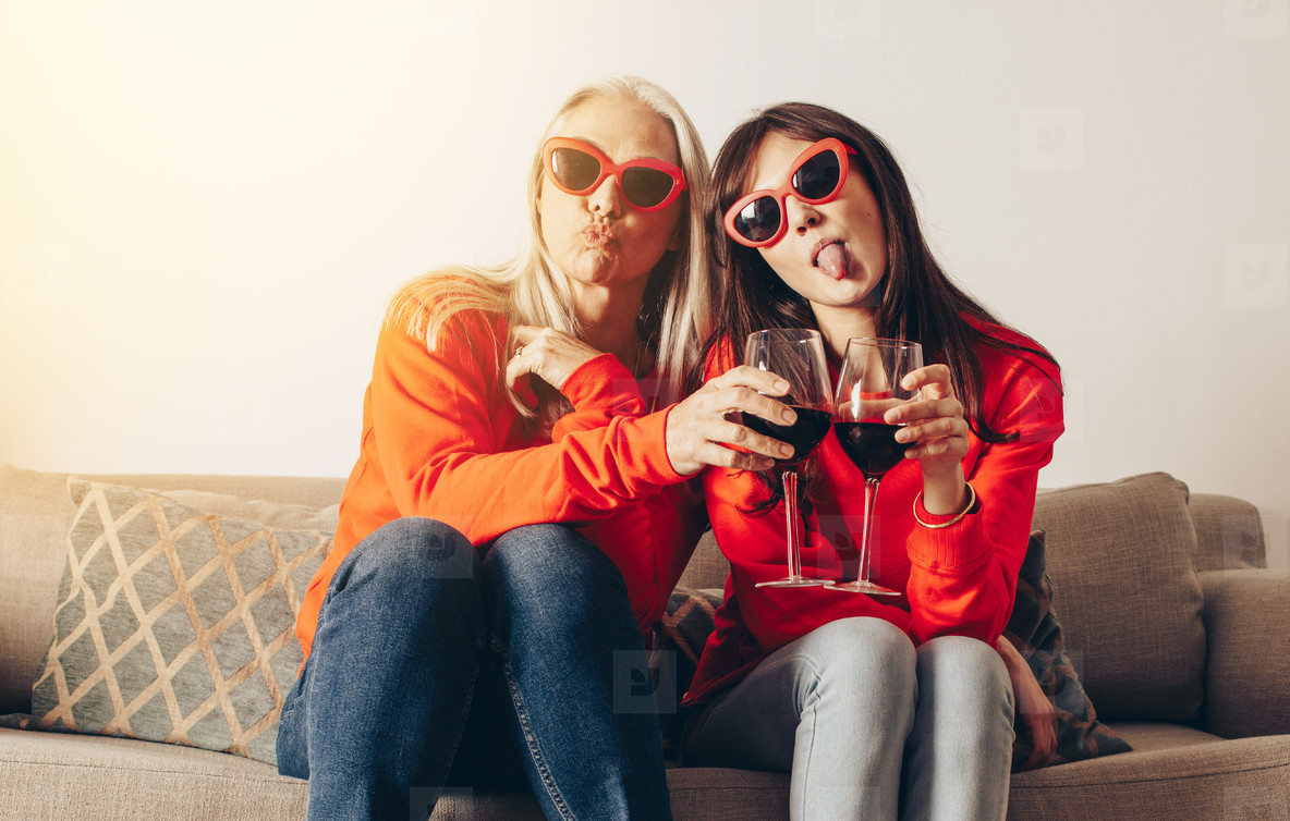 Two women sitting on couch with glass of wine making faces