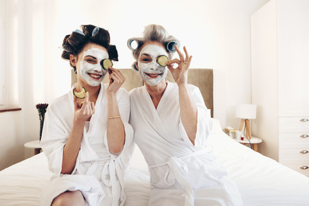 Two women in bathrobes with beauty face pack sitting on bed