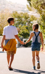 Boy and girl in love walking on street holding hands