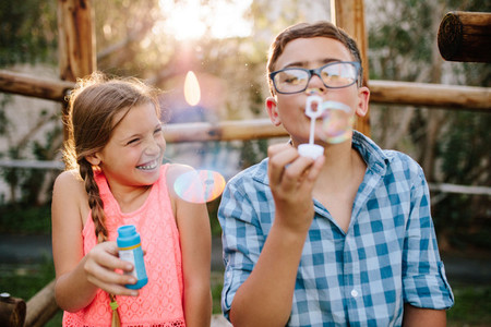 Young boy and girl having fun blowing soap bubbles